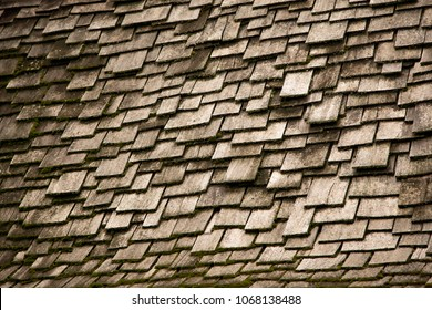 Abstract background of uneven and mismatched antique wood shingles on an old country cottage and European style farm house