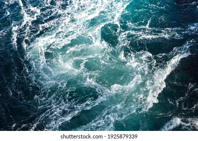 Abstract background. The waves of the sea water meet with underwater pointed rocks, forming whirlpools. Whirlpools in the area of the Norwegian city of Bod?. Norway - Shutterstock ID 1925879339