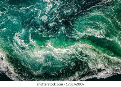 Abstract background. Waves of water of the river and the sea meet each other during high tide and low tide. Whirlpools of the maelstrom of Saltstraumen, Nordland, Norway - Shutterstock ID 1738763837