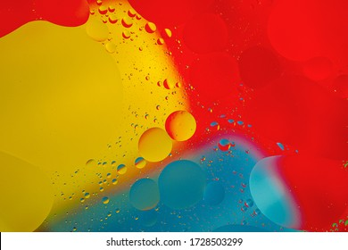 Abstract background with yellow, red, blue circles in oil. Distortion in water with drops of oil. Bright abstraction, ultraviolet. Circles on the water.
