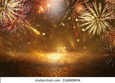 abstraktes Gold, schwarz-goldener glänzender Hintergrund mit Feuerwerken. Weihnachtsabend, 4. Juli-Urlaubsszenario