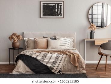 Abstrakte schwarze Ölmalerei auf leerer beiger Wand eines gemütlichen Schlafzimmers