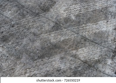 Abstract black and white tire tracks background with tire marks on cement floor .