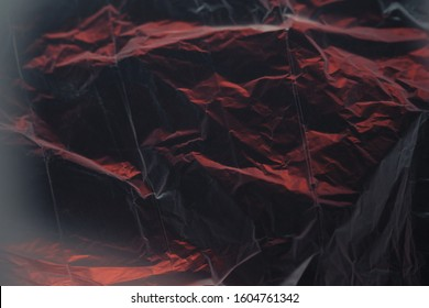 abstract black-and-red texture made of crumpled polyethylene