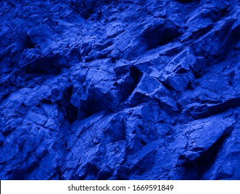 Abstract blue background. Toned mountain texture. Close-up. The combination of bright blue and rough stone surface. Colorful rock background.    Fantasy, science fiction, surreal.