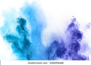 Abstract blue dust explosion on  white background. Abstract blue powder splattered on clear background. Freeze motion of blue particles splash. Painted Holi.