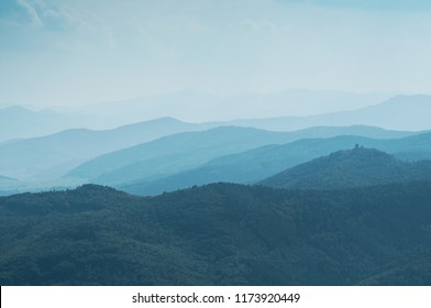 Abstract blue Landscape with Silhouettes of Misty Mountains and Forest. Multilevel Mountain Range in the Background and a Dense Forest in the Foreground