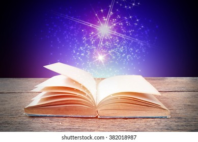 Abstract blue magic book on wooden background