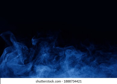 Abstract blue smoke moves on black background. Mystical swirling smoke rolling low across the ground.