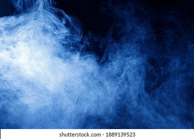 Abstract blue smoke moves on black background. Swirling smoke.
