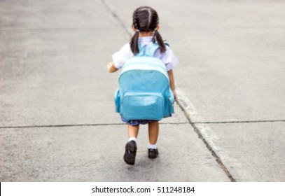 abstract blur back of ponytail little asian girl walking to school