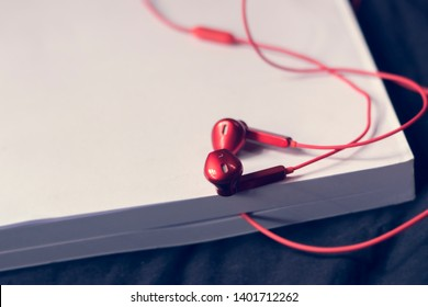 Abstract blur background audio book concept,Red earphones with white books.Learning through sound,Without having to read from texts.Innovation and Education Technology 21st century.Selective focus.