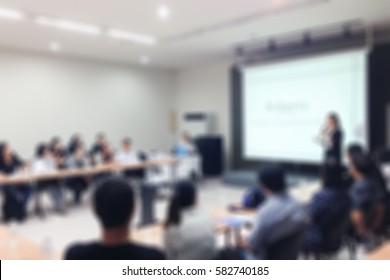 abstract blur background of business presenter in meeting room with audience