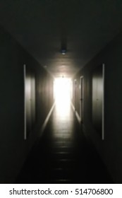 Abstract blur background of dark long corridor with symmetry wall, end walkway with light