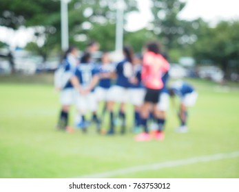 Abstract blur background, girls football team talk in the field on sunny afternoon