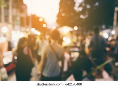 abstract blur background people walking in food festival with warm lights