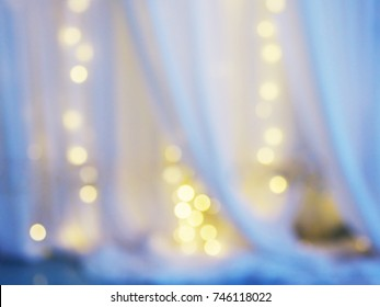 Abstract blur background of white curtain with light bulb bokeh at window in bedroom. Good night, sweet dream and relax concept.