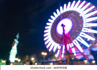 abstract blur bokeh night harbor lights background with ferris wheel