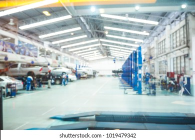 Abstract blur car technicians repairing cars in workshop service station background.