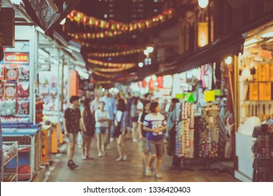 Abstract blur Crowds walk through a Chinatown market at night in Singapore