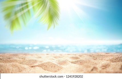 Abstract blur defocused background, nature of tropical summer beach with rays of sun light. Golden sand beach, sea water and palm leaves against sky. Copy space, summer vacation concept.