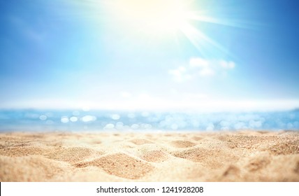 Abstract blur defocused background, nature of tropical summer beach with rays of sun light. Golden sand beach, sea water against blue sky with white clouds. Copy space, summer vacation concept. - Shutterstock ID 1241928208