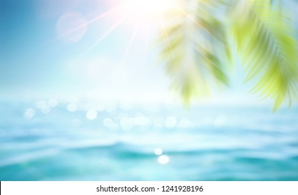 Abstract blur defocused background, toned gently blue, nature of tropical summer, rays of sun light. Beautiful sun glare on sea water and palm leaves against sky. Copy space, summer vacation concept