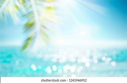 Abstract blur defocused background, toned gently blue, nature of tropical summer, rays of sun light. Beautiful sun glare on sea water and palm leaves against sky. Copy space, summer vacation concept.