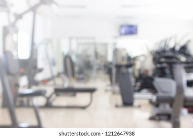 Abstract blur fitness gym with equipment for background.