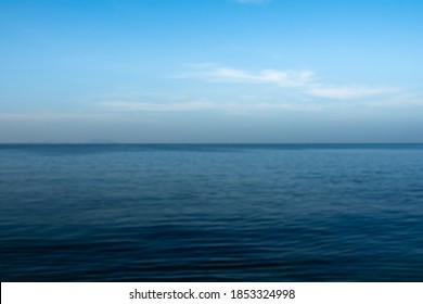 Abstract blur image of blue sea and clouds on sky background usage. Seascape with sea horizon and almost clear deep blue sky. Wallpaper, Background.