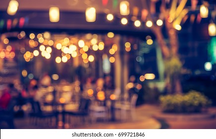 Abstract blur image of Cafe or Restaurant in night time with bokeh for background usage . (vintage tone)