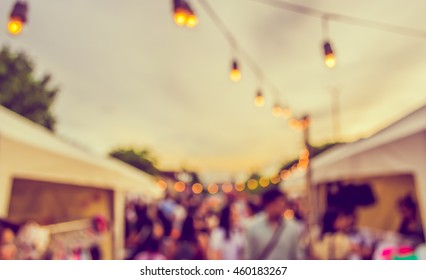 abstract blur image of food stall at day festival for background usage . (vintage tone)