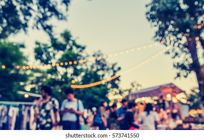 abstract blur image of  food stall at day festival  in garden with bokeh for background usage . (vintage tone)
