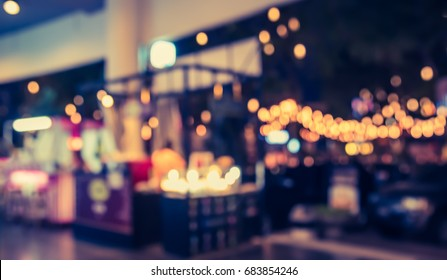 abstract blur image of Food stall at night market festival for background usage . (vintage tone)