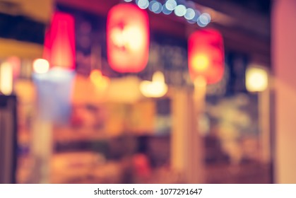 Abstract blur image of Japanese Restaurant in night time with bokeh for background usage . (vintage tone)