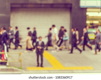 Abstract blur image of People crossing at street in city with bokeh for background usage . (vintage tone)
