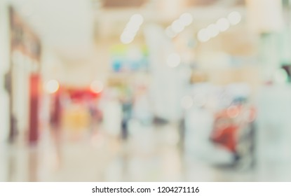 Abstract blur image of People at Motor show exhibition in hall with bokeh for background usage . (vintage tone)