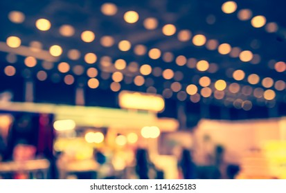 Abstract blur image of People walking at Shopping mall or Exhibition hall with bokeh for background usage . (vintage tone)