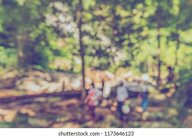 Abstract blur image of people walking in green garden with bokeh for background usage . (vintage tone)