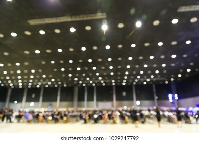 Abstract blur many people in an exhibition hall background.