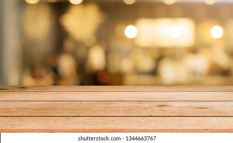 abstract blur night cafe restaurant with bulbs light and wooden tabletop counter for ads,show,promote on display screen