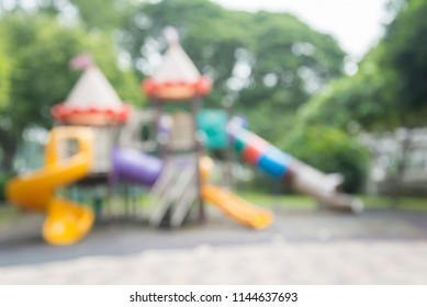 Abstract blur outdoor children playground in green nature city park bokeh background
