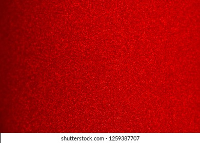 Abstract blur paper deep red foil background for Merry Christmas and Valentine's Day.  Gradation dark red shiny with sparkle metallic texture background. top view