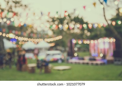 Abstract blur people in night festival city park bokeh background - retro tone