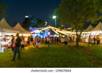 Abstract blur people in outdoor night festival city park bokeh background. Summer festival holiday or celebration party concept.