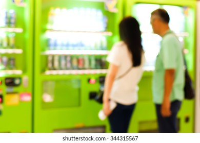 Abstract blur of people paying for the drinks from the vending machine