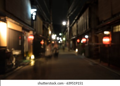 Abstract blur people walking on narrow street of wooden store and restaurant with lighted lanterns at night in Kyoto, Japan