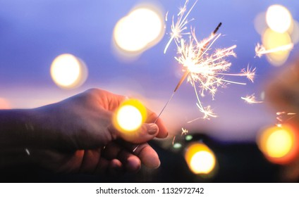 Abstract blur sparklers and bokeh for celebration background,Motion by wind blurred woman hand holding burning sparkle on nature purple twillight sky background.Winter vintage film grain filter style.