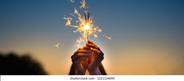 Abstract blur sparklers for celebration background,Motion by wind blurred woman hand holding burning Christmas sparkle on nature and twillight sky background.Winter vintage film grain filter style.