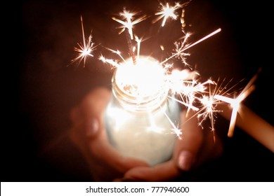 Abstract blur sparklers for celebration background,Motion by wind blurred woman hand holding glass bottle burning Christmas sparkle  and dark night sky background.Vivid color night grain filter style.